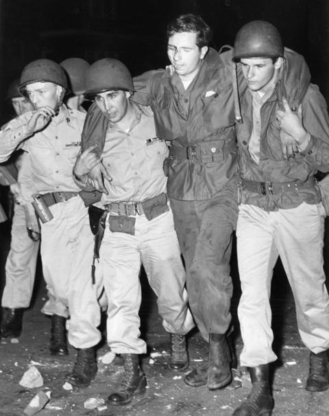 National Guardsmen assist Cpl. Donovan Gibson after he was hit in the face by a brick thrown by a rioter in 1951.