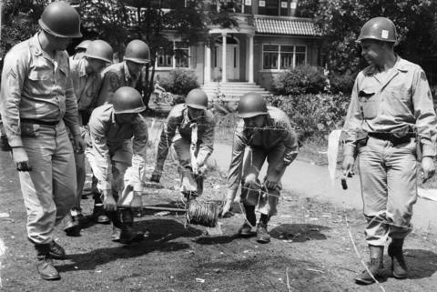 National Guardsmen are seen stringing barbed wire around the area where rioters severely damaged an apartment building two nights earlier in 1951.