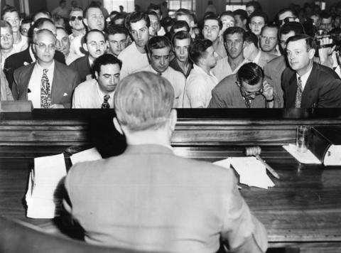 Grim-faced defendants stand in front of Police Magistrate E. Marvin Capouch answering to charges resulting from rioting at a building where an African-American family had rented an apartment in 1951.