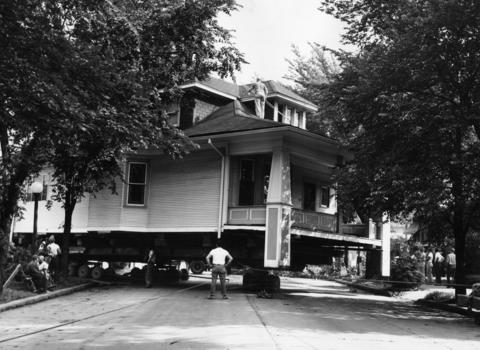 A 10-room house is moved off its lot at 2502 Austin Blvd. to a new location down the street in 1957. The house is being moved to make way for a new church to be constructed on the site.