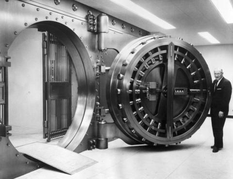 Frank J. Vales, president of Western National Bank of Cicero, stands next to the bank's vault in 1963.