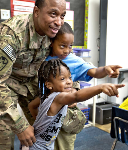 Armstrong School for the Arts, Sgt. Major James Holmes surprises his son inside his class room this morning. U.S. Army Sgt Major James Holmes has been deployed to Afghanistan for the entire school year. Adrian 4 yrs. and Aiden 8 yrs. point out where their mother is to their father during the this mornings reunion.