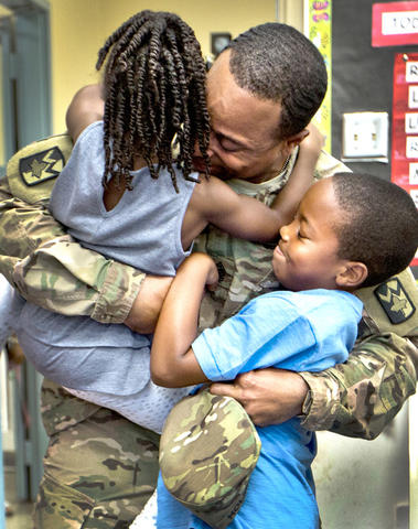 Armstrong School for the Arts, Sgt. Major James Holmes surprises his son inside his class room this morning. U.S. Army Sgt Major James Holmes has been deployed to Afghanistan for the entire school year. Adrian 4 yrs. and Aiden 8 yrs. jump up on their father on his return from being deployed to Afghanistan.