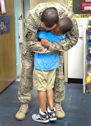 Armstrong School for the Arts, Sgt. Major James Holmes surprises his son inside his class room this morning. U.S. Army Sgt Major James Holmes has been deployed to Afghanistan for the entire school year. Aiden 8 yrs., gets a big hug from his father Sgt. Major James Holmes this morning.