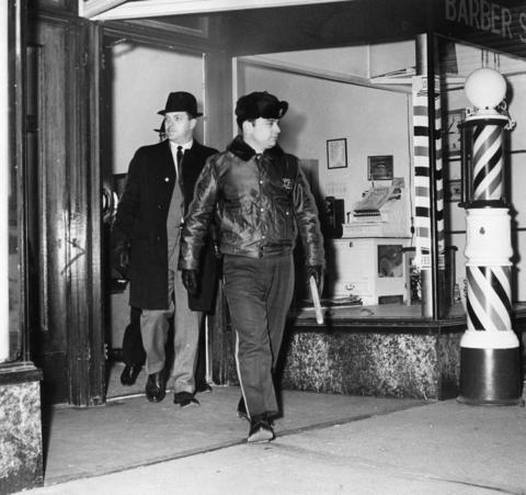 Police officers emerge from a barbershop after notifying the proprietor that vigilance against illegal operations will increase under orders of Sheriff Richard B. Ogilvie in 1964.