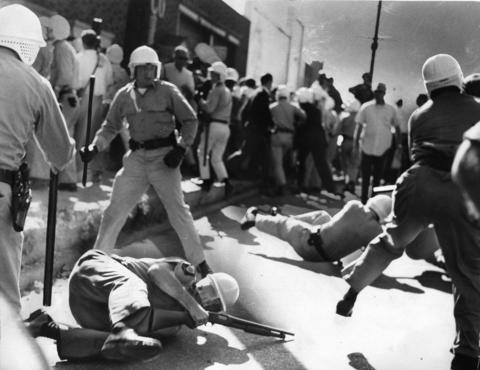 State troopers are bowled over by people who had been heckling civil rights marchers in Cicero in 1966. This happened as a brief free-for-all broke out near the end of the march.