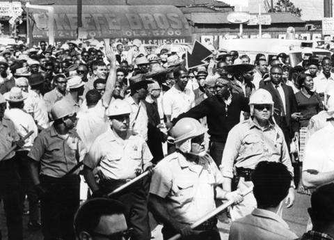 Helmeted policemen with their clubs in hand serve as protection on both flanks of civil rights marchers as they clog Cicero Avenue from curb to curb in 1966. Leading the marchers is Robert Lucas (arrow).