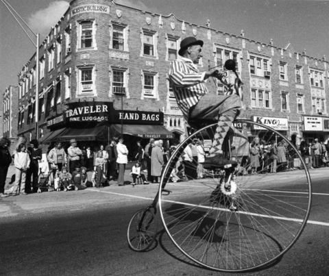 A cyclist in vintage dress perches atop a high-wheeler during the 12th Annual Houby Day Parade on Cermak Road in 1981.