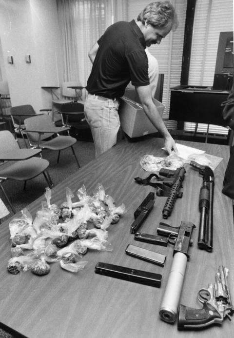 FBI agent Tom Bridges inspects weapons and drugs seized in a raid on a Cicero apartment in 1984. Two pounds of heroin and a silencer-equipped machine gun were among the items found.