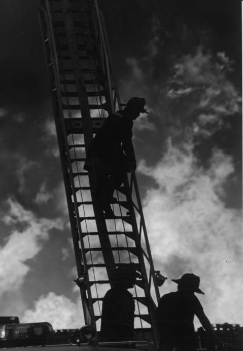 A firefighter looks as if he is on a stairway to hell as flames billow out of an industrial complexin 1987.The five-alarm fire injured two firefighters.