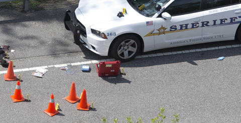 Cones mark evidence accompanied by medical items used to try to save the person shot by a York/Poquoson Sheriffs deputy after the suspect pulled a gun on the deputy during a warrant check on Ft. Eustis Blvd. in York County Wednesday morning, June 24, 2015.