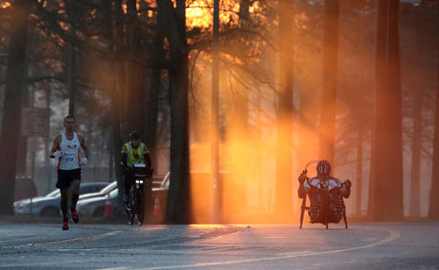 One City Marathon runners and a hand cyclist prepare for the turn on Warwick Blvd. Sunday, March 15, 2015.