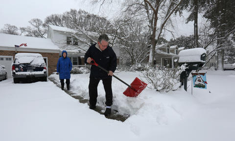 Donna Pultz of Newport News stands behind her husband Richard Pultz as he shovels his way to his morning newspaper and the mailbox on West Governor Drive in Newport News. The two Newport News retirees had just returned from a Carribean cruise and were greeted with Thursday's snow.