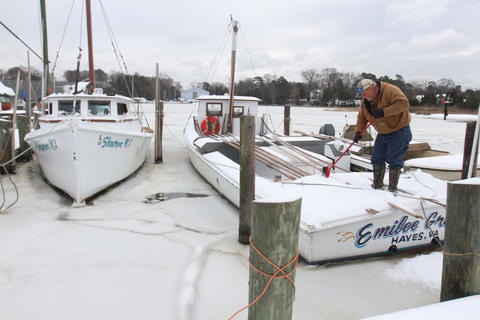 D.W. Marshall sweep his deadrise clearof snow tuesday morning at Deep Creek. Marshall didn't hold out any hope for being able to get back to harvesting oysters this week due to the freezing weather. No Mags, No Sales, No Internet, No TV