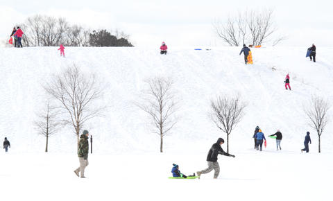 Sledders don't let the cold deter them as they take to the hills at Riverview Farm Park in Newport News Tuesday.