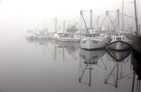 Workboats rest fogged in on Deep Creek in Newport News early Thursday morning.