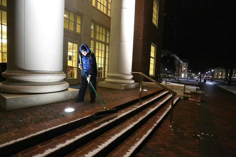 Dave Waynick sweeps the steps of the Trible Library clearing the way for students early Tuesday morning.