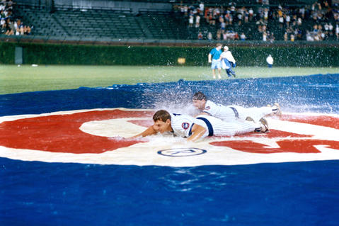 Cubs Jody Davis, front, and Les Lancaster slide on the rainy field cover during a weather delay.