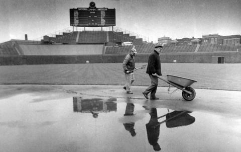 Grounds crew members at Wrigley Field work to remove water from the infield before the Cubs' opener against Montreal.