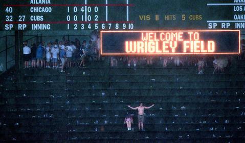 A couple of fans endure the heavy downpour during a rain delay.