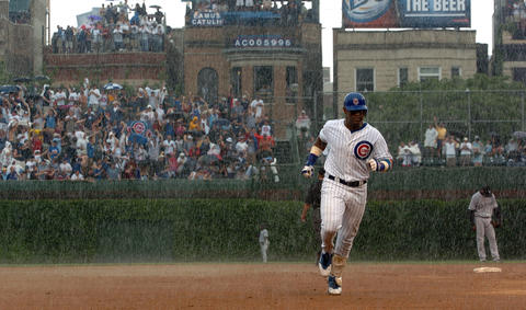 The Cubs' Sammy Sosa circles the bases for a solo home run in the pouring rain in 2004.