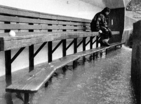 Wrigley guard Ed Keiffer sits in a waterlogged dugout during a rain delay as the Cubs play the Rockies in a double-header in 1997.