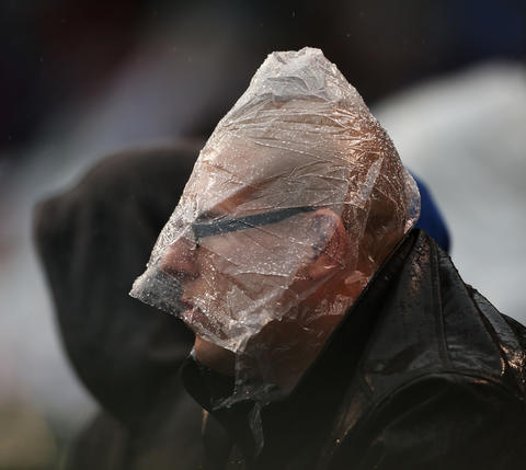 Fan Mathew Ruskuls makes use of a poncho during a rainy Cubs game against the St. Louis Cardinals in 2012.