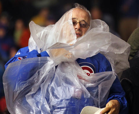 A Cubs fan suits up as the rain starts during a game against the New York Mets in 2011.