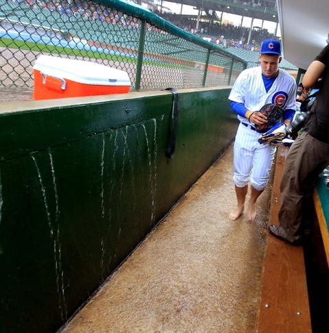 The Cubs' Anthony Rizzo walks barefoot through the flooded dugout as the Cubs host the Arizona Diamondbacks in 2012.