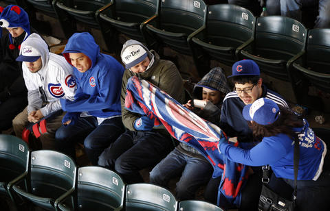 Cubs fans fight for a blanket as they brave the cold during a game in 2012.