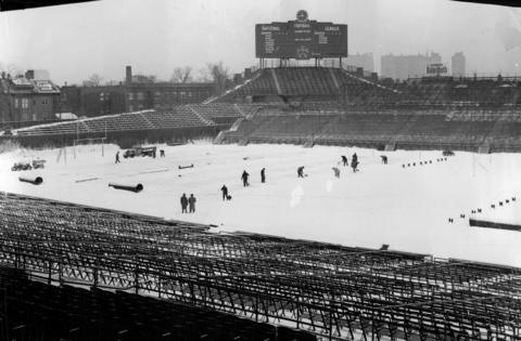 The grounds crew works to clear snow from the field before the Bears play the Lions in 1950.