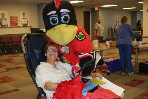 Barb Dellinger of Park Ridge gets a friendly visit from Blackhawks mascot Tommy Hawk at the hockey team's sponsored LifeSource blood drive in Rosemont.
