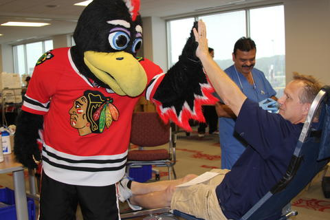 Blackhawks mascot Tommy Hawk shows some love to Oswego's Tim Zot as a thank you for donating blood at the hockey team's LifeSource drive at the blood service headquarters in Rosemont.