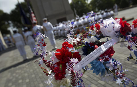 A wreath with an attachment listing the sequence of events on September 11, 2001 is held by a USS Abraham Lincoln sailor prior to being placed beside the Victory Arch during ceremonies in Newport News on Friday September 11, 2015. Sailors from the carrier gathered at the monument to pay their respects on the anniverary of the terrorist attack.