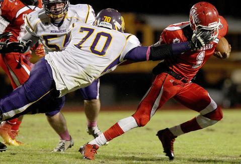 Menchville's Kenneth Kirby gets a handful of facemask as he drings down Jovonn Quillen during the second quarter Thursday.