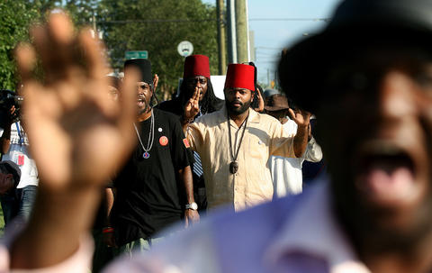 Khori Allende-El of the Moorish Science Temple of America marches with about forty peaceful protestors up Jefferson Ave. to the Newport News Police headquarters Wednesday. The march was held to draw attention to the situation in Ferguson, Missouri and to gun violence in general.