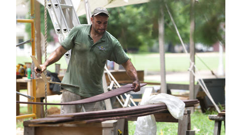 Holding a framing square, Ted Boscana sets about the task of installing primed siding on the Scale House.