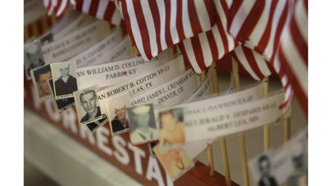 Pictures of the 134 that lost their life on the USS Forrestal during the 1967 flight deck fire are attached to flags as part of a display for the anniversary memorial.