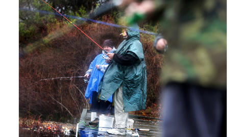 After volunteering to help populate Lake Biggins as part of the urban trout program run by the Virginia Department of Game and Inland Fisheries, James Landreneau, background, and Roy Turnage, despite light rain, have fun fishing for the newly released rainbow trout. At least 300 fish were released and they came from Coursey Springs Hatchery.