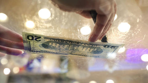 At the Craft House on Duke of Gloucester Street, Carol Beran uses a counterfeit money detector pen to check a twenty dollar bill.