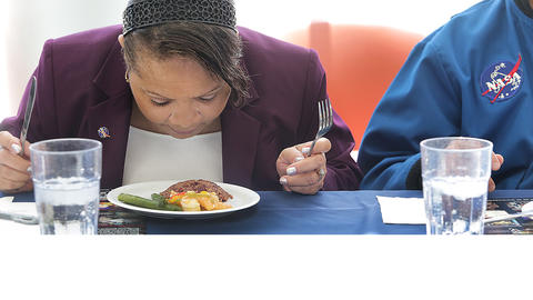 Culinary Challenge Judge Junilla Applin lowers her face to closely examine the possible astronaut food for visual detail and aroma.