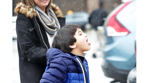 George Orphanidys' favorite Christmas movie is the Christmas Story, so snowfall in the Hilton Food Lion parking lot gave him a chance to try and catch a flake on his tongue; his mother Michelle is amused.