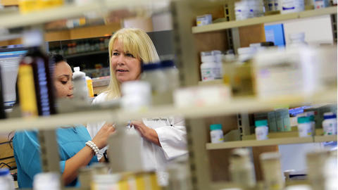 (Primary photo) Ashley Davis, left, and Karen Russo, R Ph, discuss one of the pharmaceuticals from the well-stocked shelves. The pharmacy component of the Hampton City Schools Employee Health and Wellness Center just recently opened and has generics costing as low as two dollars. The clinic is in the same building making taking care of your health more convenient and inexpensive.