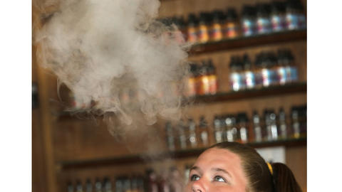 Nicole Forney blows a vapor cloud; behind her is a selection of product the store carries.