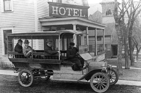 A horse carriage mounted on a truck chassis hauls tourists in front of the Grice Hotel in Antioch in 1916.