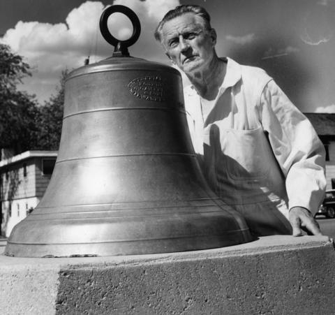 Fireman John Horan stands with the 1896 fire bell, which called villagers to the fire pumper and bucket brigades in 1963.