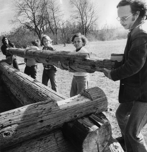 October 1974: Antioch Community School seventh and eighth graders help teacher John Estep build a log cabin using old telephone poles. The students, reverting back to pioneer days living, are also building their own furniture and grinding their own corn.