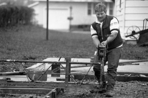 April 1991: Gary Russell gets ready to start pouring cement outside Calvary Baptist Church where he is helping to put in pavement for a parking lot.