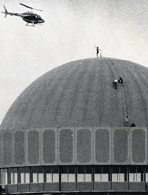 1975: Sixteen stories above Bolingbrook, Michele Mauthe, 18, tap dances on the domed roof of Old Chicago as cameramen in a helicopter film. The stunt was part of a commercial for the new shopping center and amusement park at U.S. Hwy. 53 and the Stevenson Expressway. A recent graduate of Laural Grant High School in Lisle, Mauthe answered a classified ad seeking someone who did not suffer from acrophobia, and was chosen from 100 applicants.