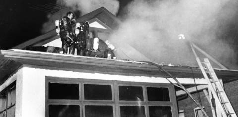 1972: Firefighters try get inside the burning attic of a Brookfield home. Two young girls were killed and their brother was seriously burned in the fire.
